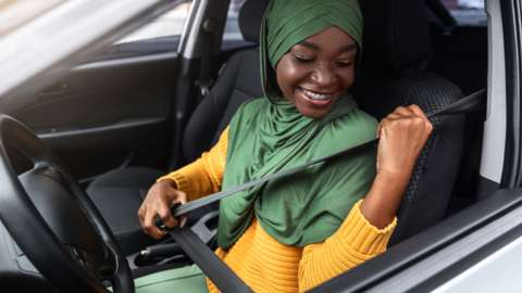 A young woman puts on her seatbelt in driving seat