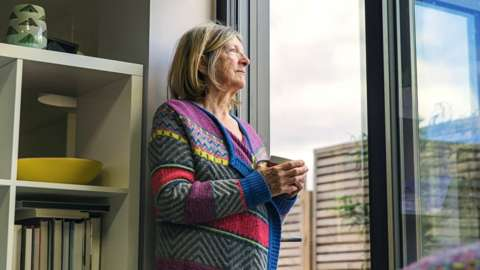 A senior woman looking through a window in her home on a wet day