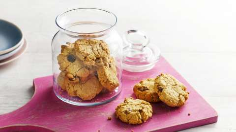 A glass jar of oat cookies on a pink wooden board