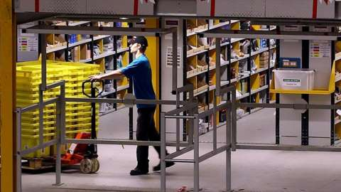 An employee moves stock in an Amazon warehouse