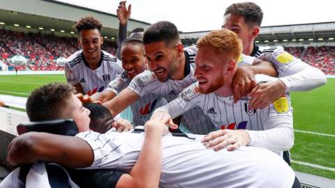 Rhys Porter is embraced by Fulham players