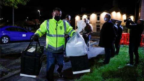 A member of the elections commission carries bags with ballots at Mill House Leisure Centre, in Hartlepool,