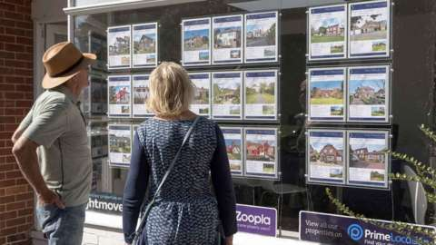 Couple looking in an estate agents' window