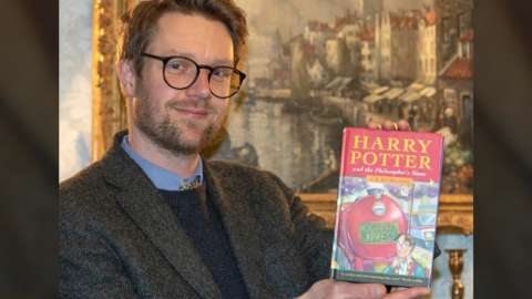 Jim Spencer holding up first edition Harry Potter book