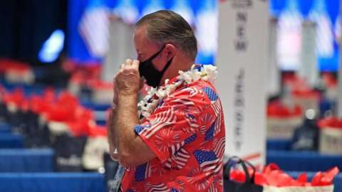A delegate wears a mask and a Hawaiian flag covered in US flags