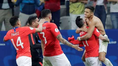 Alexis Sanchez celebrates with the Chile team after scoring the decisive penalty against Colombia which sent them through to the semi-finals of the Copa America