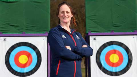 Archer Naomi Folkard poses in front of two targets after being named in Team GB's squad for Tokyo 2020
