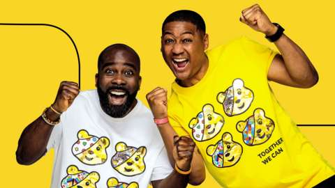 Two men excited in Children in Need shirts