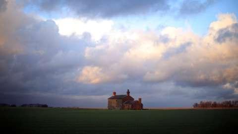 A derelict farm house adorns the horizon
