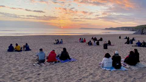 People sitting on a beach watching the sunrise