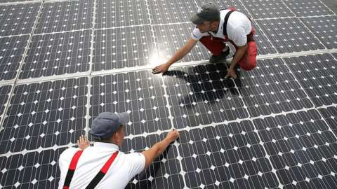 Workers install solar panels in Germany