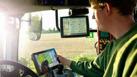 Farmer uses GPS in tractor