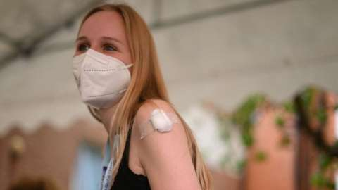 A student waits before leaving after receiving a dose of the Pfizer/BioNTech Covid-19 vaccine at a vaccination centre at the Hunter Street Health Centre in London on June 5, 2021.