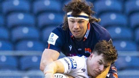 Edinburgh's Hamish Watson tackles Huw Jones of Glasgow