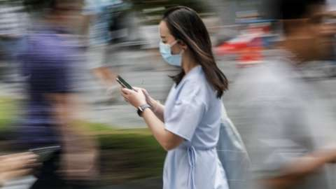 A photo taken using a slow shutter speed shows a woman wearing a protective mask as she walks through the financial district in Singapore, 07 February 2020.