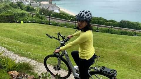 Nomia Iqbal cycling around Cornish G7 village