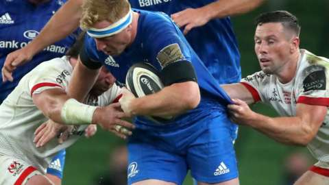Leinster's James Tracy is tackled by two Ulster players