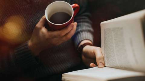 A person holds a coffee while reading a book