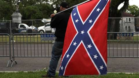 A man holding a Confederate flag across the street from the Jefferson Davis monument in New Orleans, Loiusiana