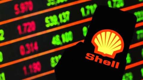 Shell logo on smartphone against stock market screen