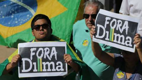 """Demonstrators hold signs that read in Portuguese """"Dilma Out"""" during a protest against the government on 16 August 2015"""