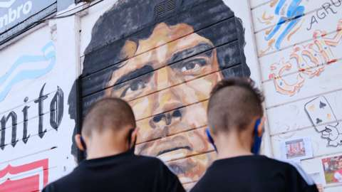 Children stand in front of Maradona mural