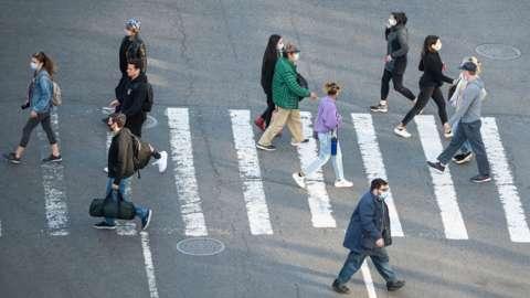 people in masks crossing road