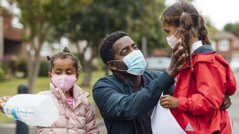 A man secures face masks on daughters