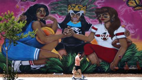 A man walks past a mural, as the coronavirus (COVID-19) disease continues, in East Los Angeles