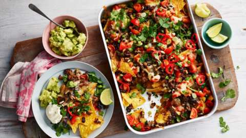 Aerial shot of a tray of nachos with bowls of lime and guacamole