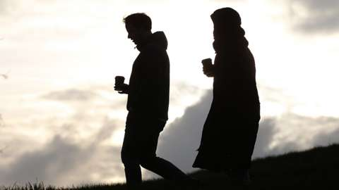 Man and woman in silhouette, walking down hillside