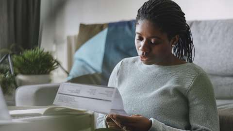 Woman looking at an energy bill.