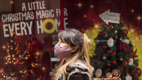 Woman walks past Christmas shop display