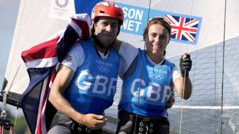 John Gimson and Anna Burnet celebrate winning silver in the mixed Nacra 17 class during the Sailing