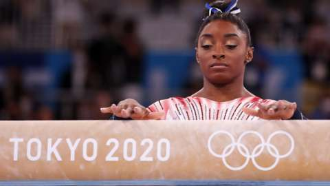 Simone Biles with her hands on a beam reading 'Tokyo 2020'