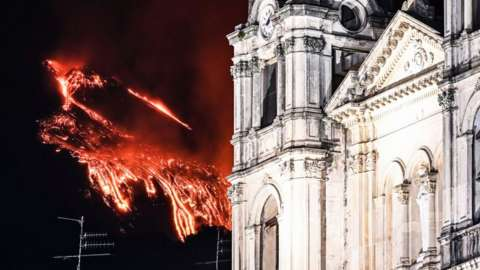 Mount Etna is erupting with cathedral in foreground