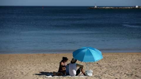 People enjoy the sun at the beach in Cascais, Portugal