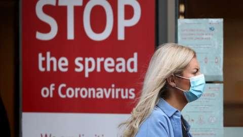 Woman walking past a Covid warning sign