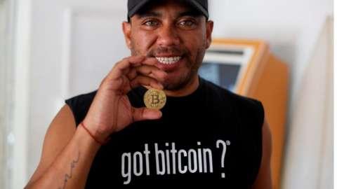 Bitcoin enthusiast Carlos Bonilla shows a physical representation of the cryptocurrency, at a Bitcoin Beach support office at El Zonte Beach in Chiltiupan, El Salvador.