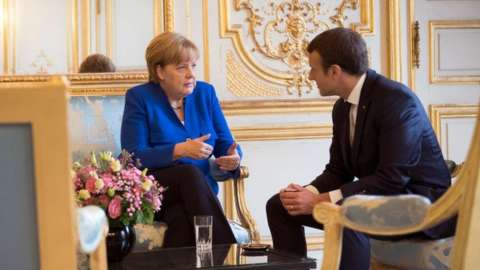 German Chancellor Angela Merkel and the French President Emmanuel Macron speak at the beginning of the Franco-German Council of Ministers at the Elysee Palace