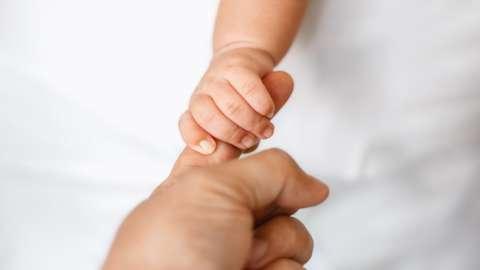 Newborn baby holding adult's finger