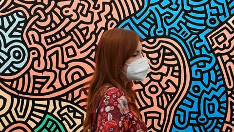"""A visitor wearing a face mask views """"Piglet Goes Shopping"""" by Keith Haring at the Frieze international art fair in London - 13 October 2021"""