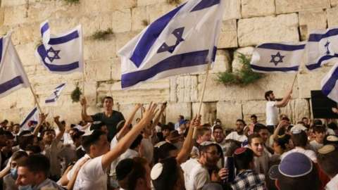 Jewish worshippers dance with Israeli national flags by the Western Wall, Judaism's holiest prayer site in Jerusalem's Old City. Photo: 9 May 2021