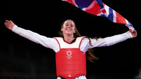 Bianca Walkden celebrating with the Union flag after securing a bronze medal