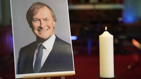 A candle and photo of Sir David Amess at church in Leigh-on-Sea