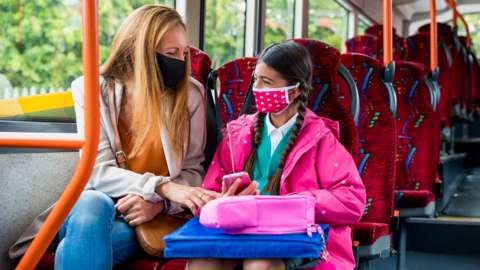 A mother and daughter wearing face coverings on the bus