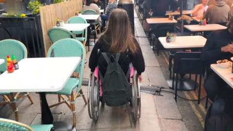 A wheelchair user navigates a crowded pavement