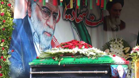 The coffin of Mohsen Fakhrizadeh is displayed in front of a painting of the assassinated nuclear scientist in Tehran, Iran
