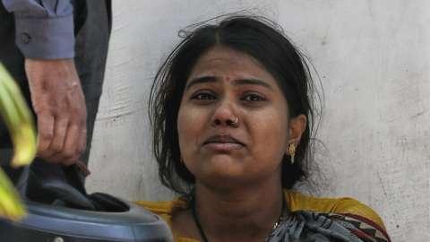 A woman crying outside a crematorium