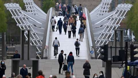 Pedestrians walk over the Millennium Bridge in London